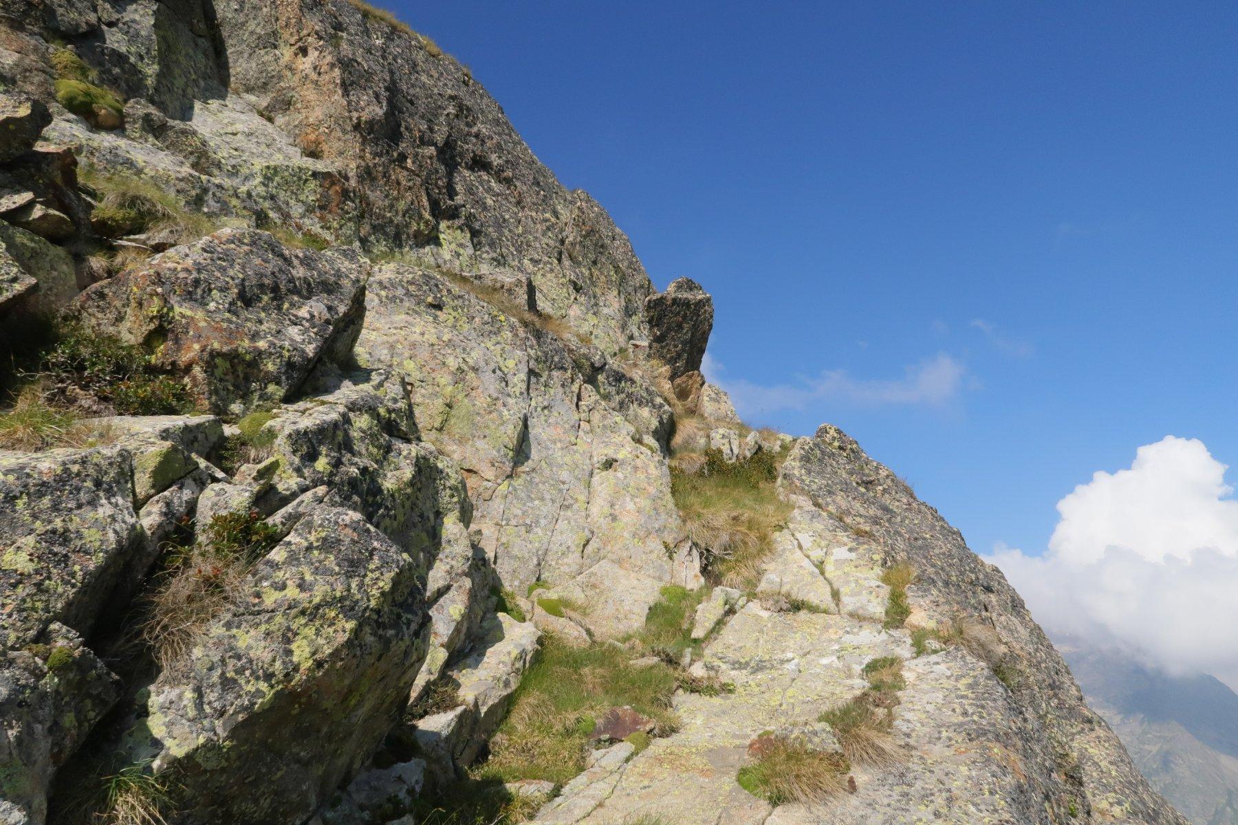 La cima della cengia ascendente che porta in cresta, con la caratteristica roccetta che si staglia nel cielo