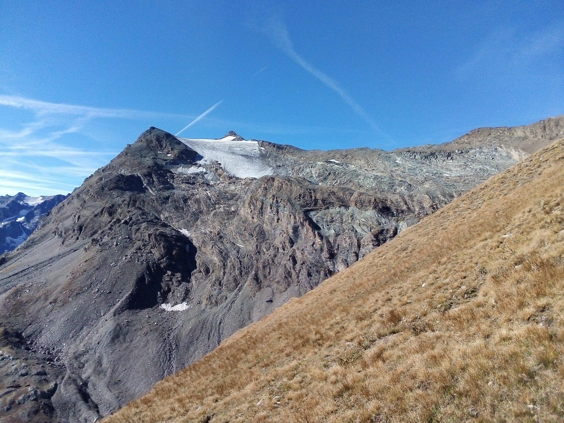 Sullo sfondo, da dietro il ghiacciao verso dx, la vetta, la cresta finale, il col Basei e l'evidente, lungo traverso in discesa fra rocce e pietraie.