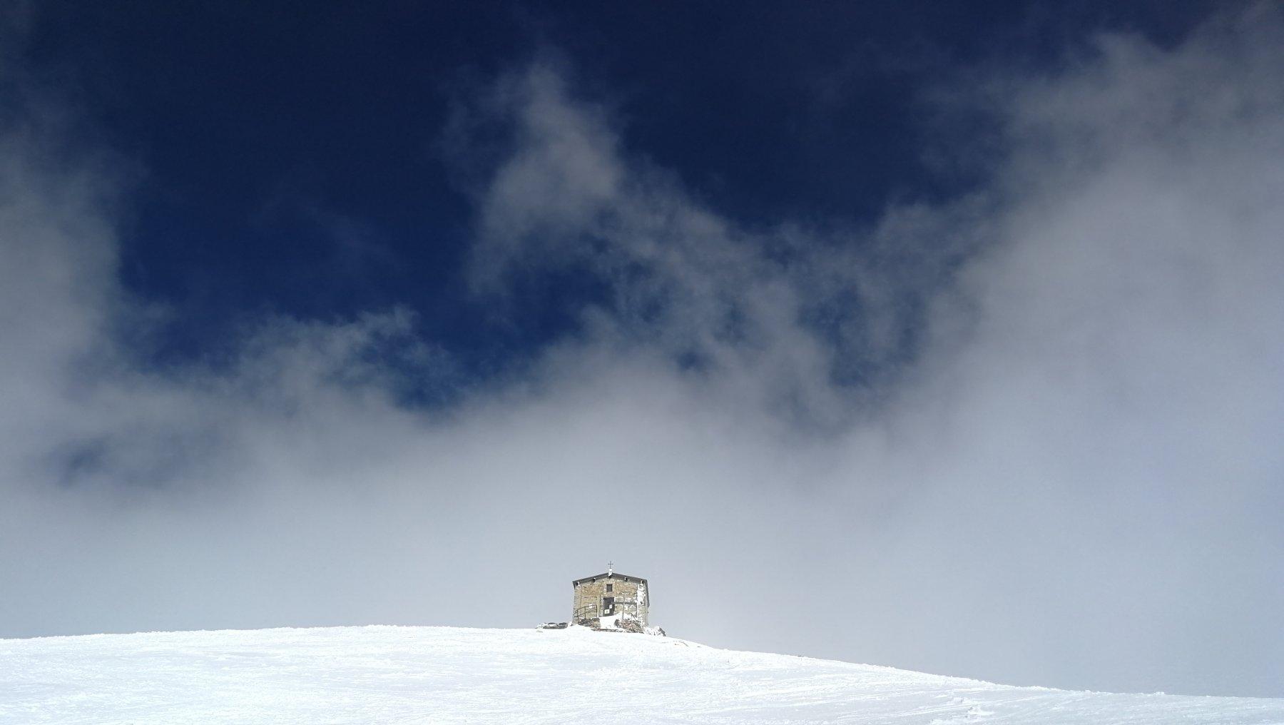 La cappella di cima (pericolante) in un attimo senza nubi, prima di esserne nuovamente inghiottita