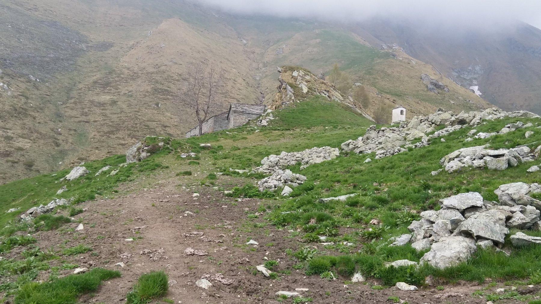 le baite di Inversetti e il pilone votivo evidente dalla sottostante  alpe diroccata a quota 1750