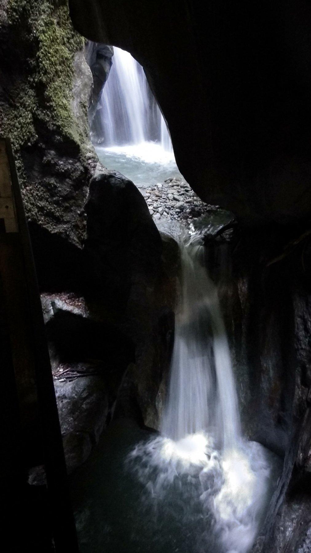 al di sotto dei macigni sono visibili le due cascatelle e la pozza d'acqua