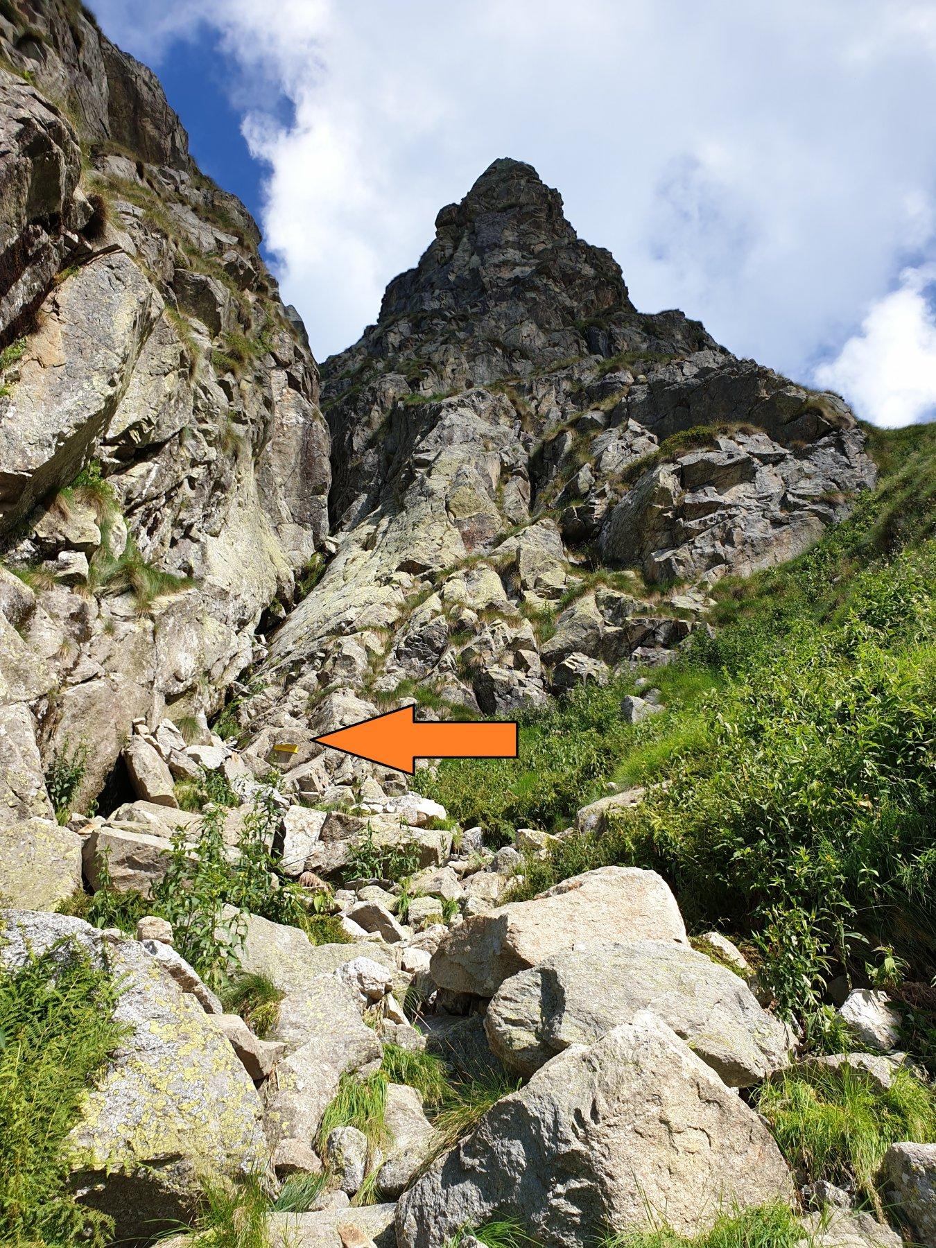 L'attacco della via a quota 1850 m. La freccia rossa evidenzia la targa mezza staccata posta alla partenza; poco più su c'è un cordone su spit.
