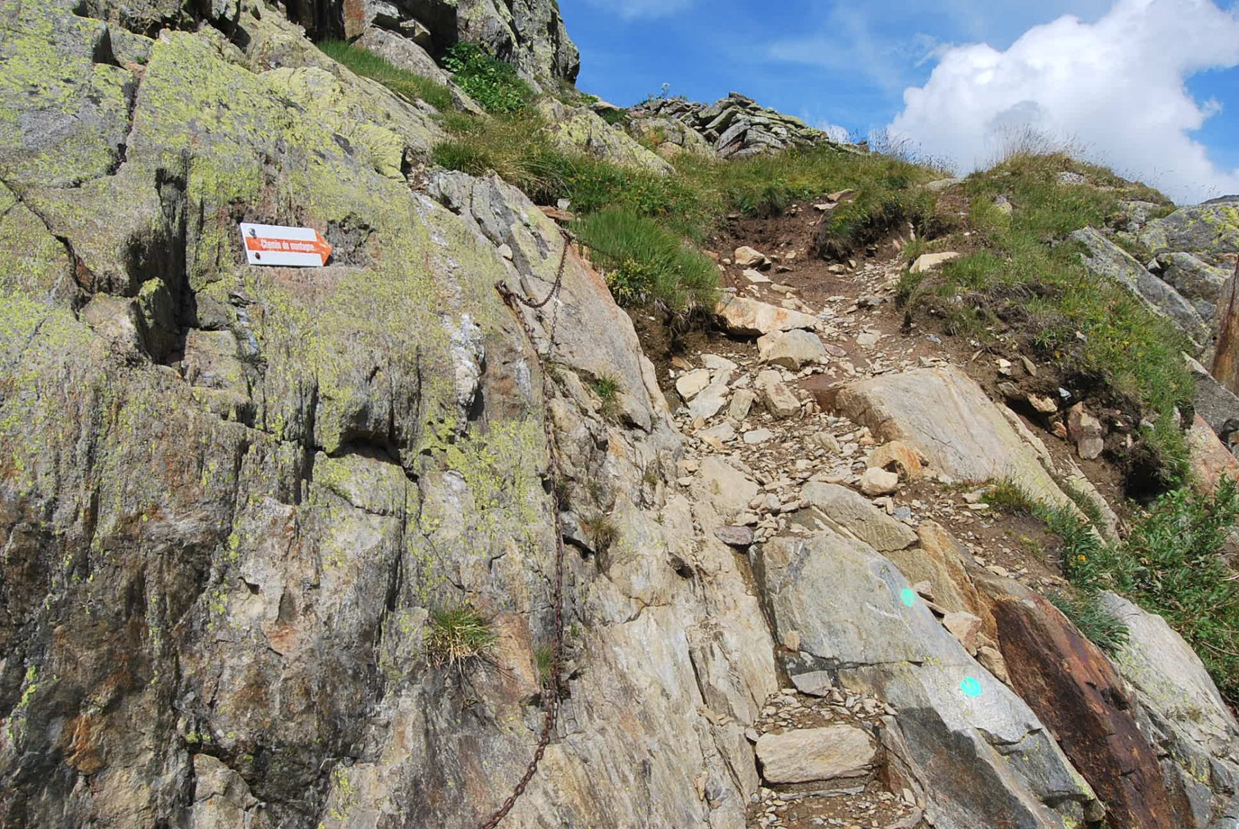 """Il sentiero alla partenza, contraddistinto dall'indicazione """"Chemin de montagne""""."""