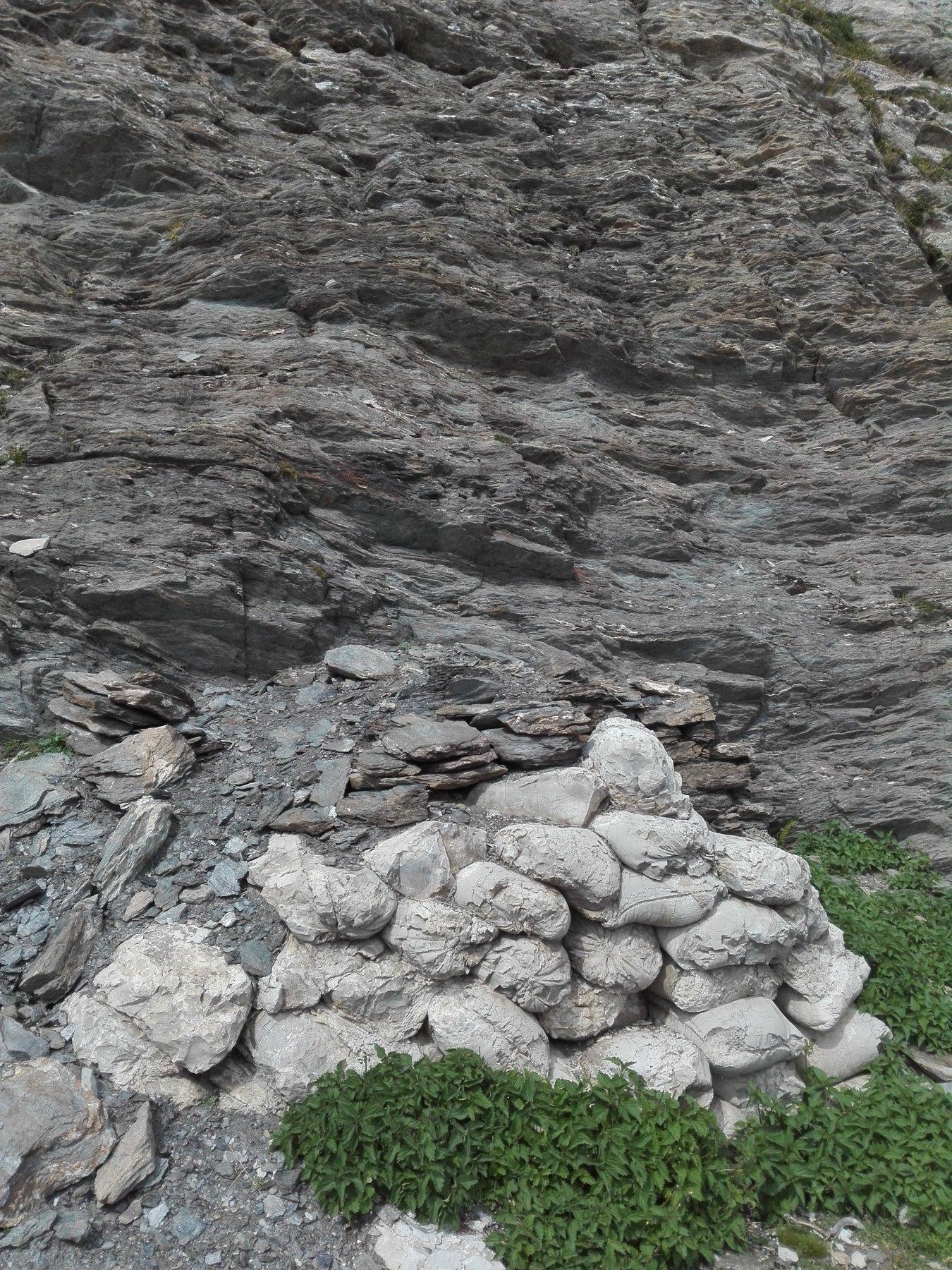 Cumulo di cemento pietrificato, sono evidenti i segni della trama e delle cuciture dei sacchi di iuta