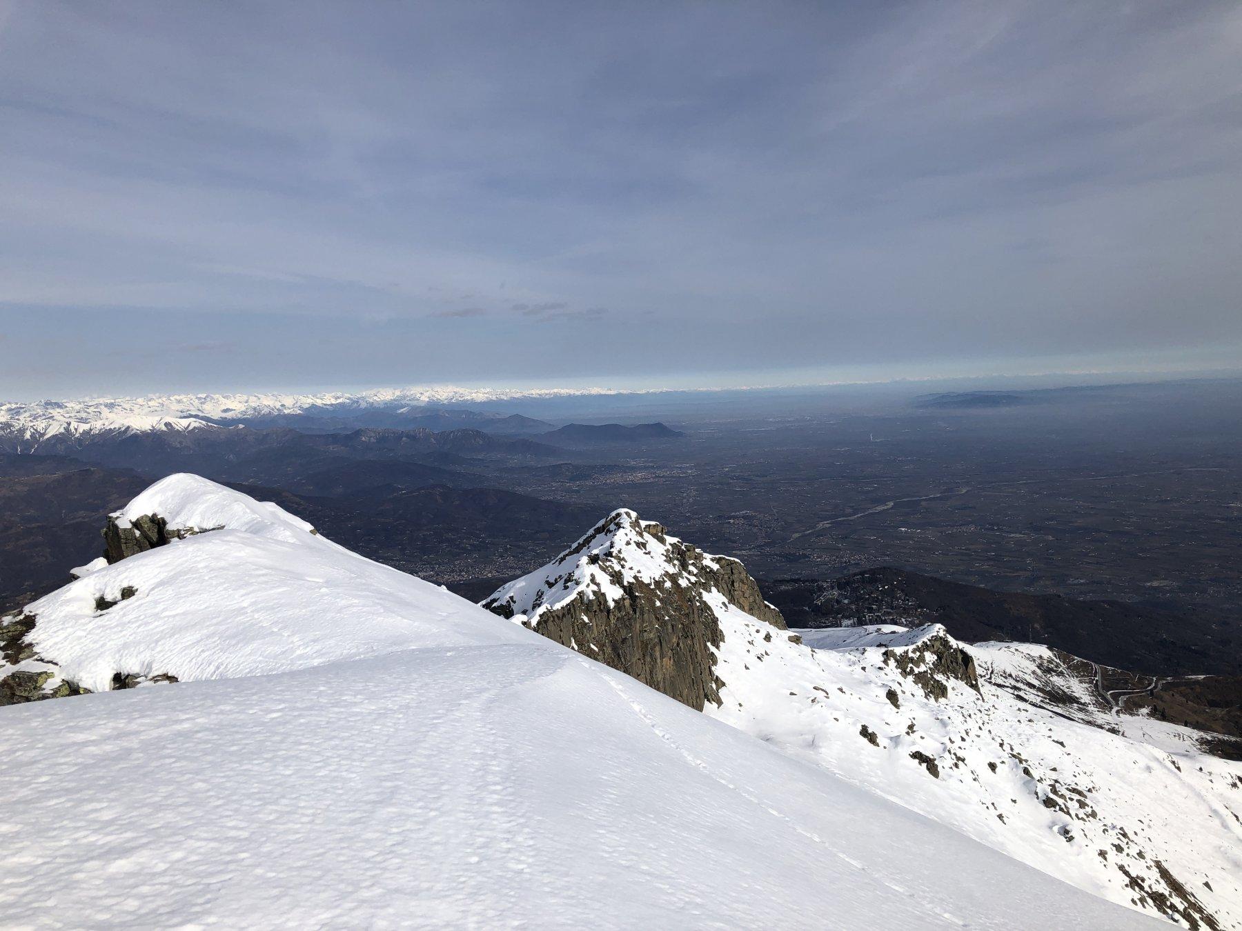 Dalla cima la cresta per arrivare al Rumella. Sullo sfondo, la piana.