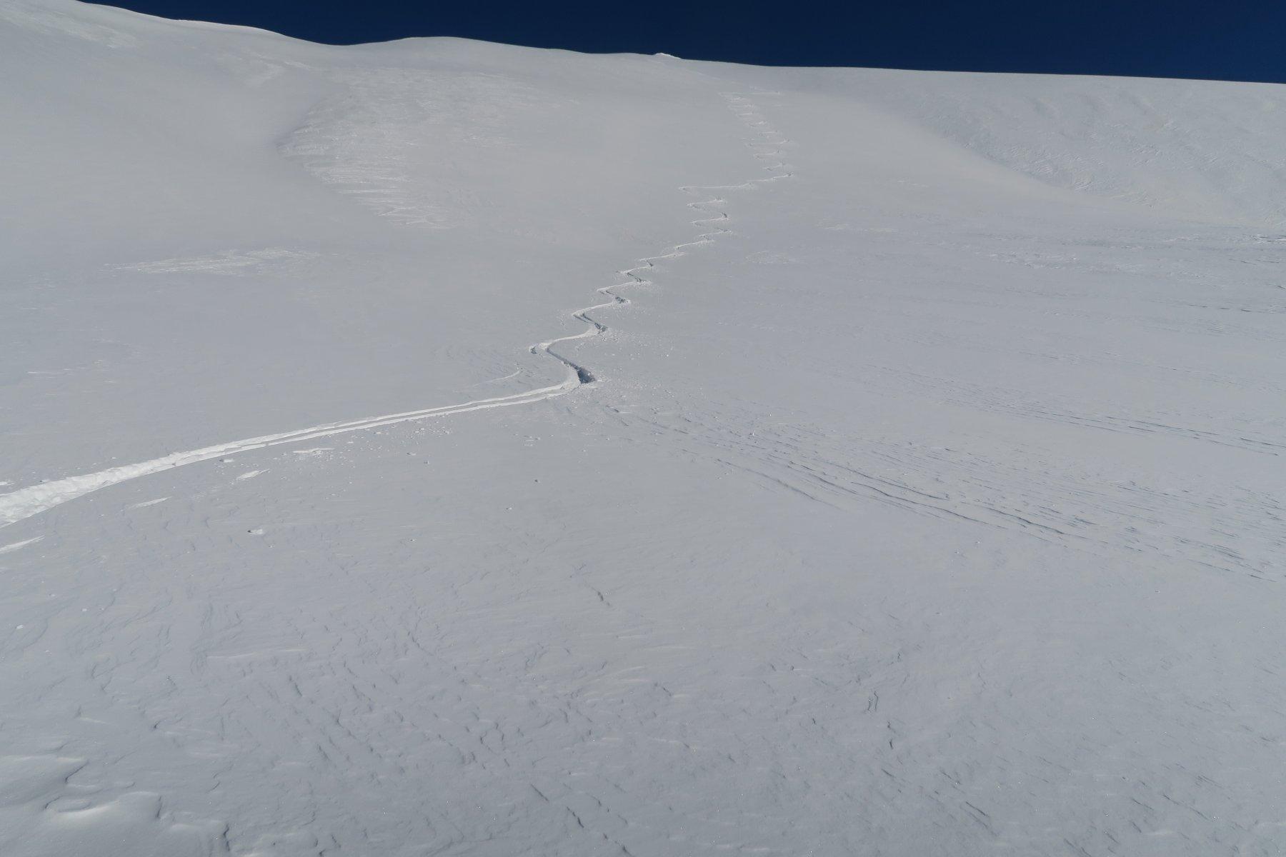 bella neve sotto la punta cercando le zone dove il vento non l'aveva spazzata