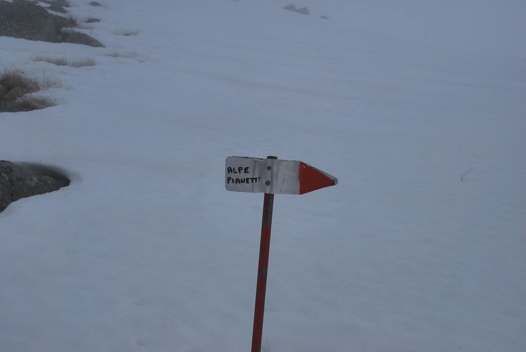 In vetta, l'indicazione per l'Alpe Pianetti con sentiero sotto la neve