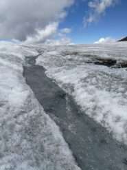 Nei pressi del colle della Resta: uno scrosciante torrentello da scioglimento sul ghiacciaio (foto E. Lana).