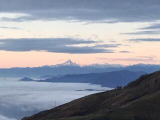 In cammino sulla sterrata il mare di nuvole sotto di noi e la vista del Monviso