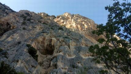 La parete dal basso. La OPEC sale poco a destra della caverna poi punta all'evidente diedro in alto, illuminato dal sole