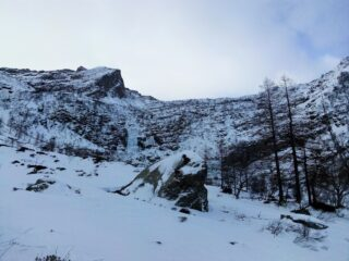 Al piano del Trione. Al centro la cascata ghiacciata. L'itinerario risale il pendio nevoso di sx, molto vicino alla bastionata, per poi curvare a dx sopra di essa, in costa.
