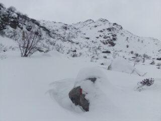 Il Gias di Mezzo spunta dalla neve (in centro), ormai sopra la bastionata. Dietro quest'alpe si vedono gli ultimi pendii di salita (poggiando a sx) e, contro il cielo, si indovina il tozzo ometto sul ciglio del piano dei laghi.