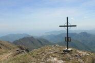 La croce di vetta; sullo sfondo la piana di Albenga.