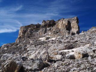 Il torrione sommitale visto dalla pietraia. La salita avviene nel primo canale da destra.