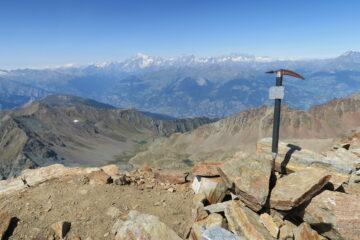 la piccozza posta sulla cima, in basso il vallone di Arbolle con il rifugio e sullo sfondo la catena del Bianco