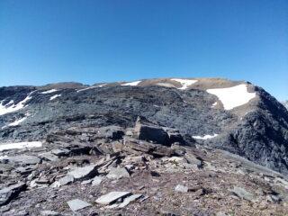 Il crestone verso il Giusalet (del quale si intravede, a sinistra, la croce di vetta) dalla cima di Bard. La segnaletica guida attraverso la zona di roccioni grigi.